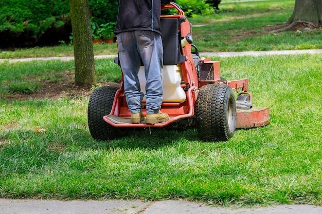 Uomo lavoratore taglio erba in estate con un giardiniere professionista che falcia il prato