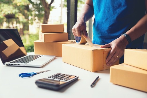 Equipaggi il servizio di consegna del lavoratore e l'imballaggio funzionante, l'imprenditore che lavora controllando l'ordine per confermare prima dell'invio del cliente in posta, le vendite online della spedizione