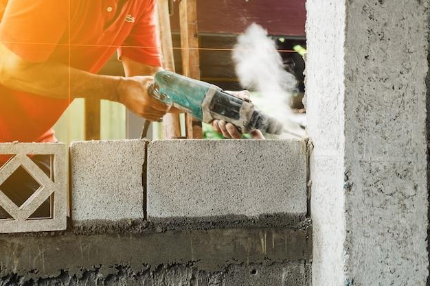 Il trapano elettrico dell'operaio dell'uomo fa la struttura del palo del cemento della casa