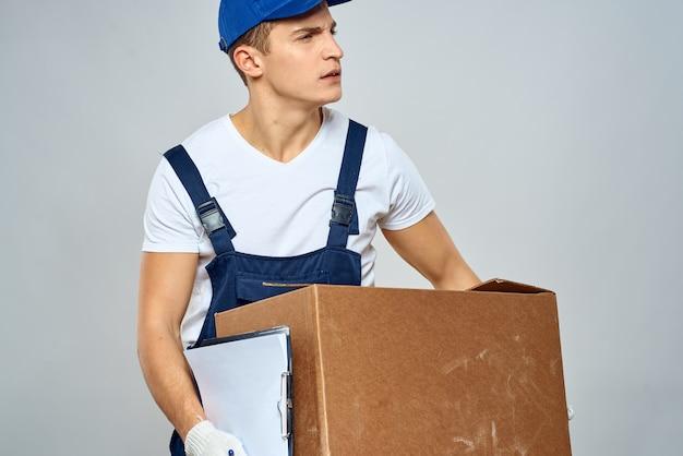 L'uomo lavoratore con scatola in mano consegna caricamento servizio servizio di imballaggio.