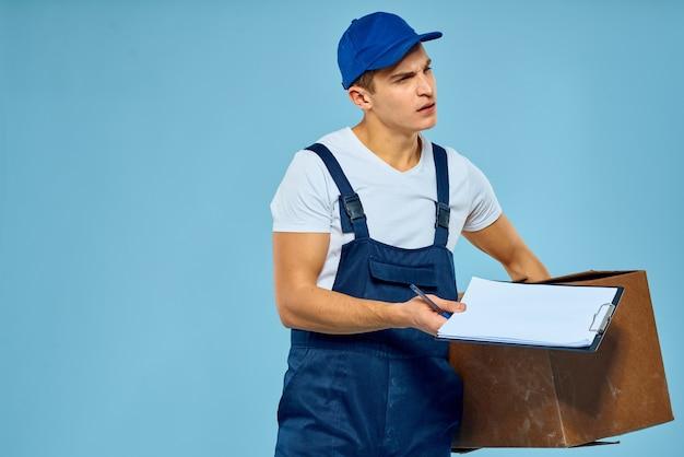Lavoratore dell'uomo con lo spazio blu di stile di vita del caricatore di consegna della scatola di cartone
