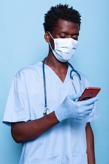 Uomo che lavora come infermiera guardando lo smartphone in mano
