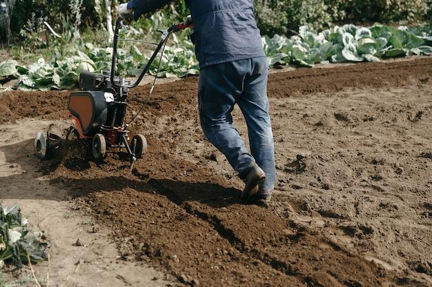 Un uomo che lavora in un giardino autunnale con una macchina meccanica da giardino. coltivatore da giardino per lavorare con il terreno