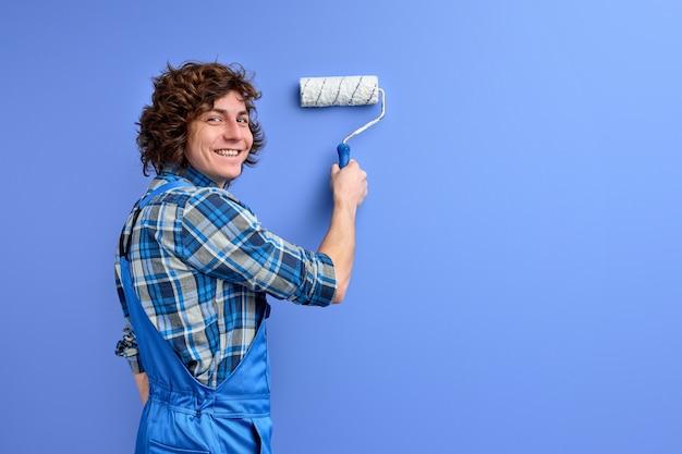 Uomo in abiti da lavoro che ripara la parete, utilizzando lo strumento di pittura.