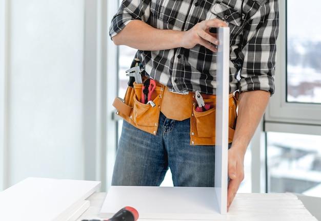Uomo che lavora alla scheda di collegamento dello scaffale durante il processo di produzione di mobili in legno in officina