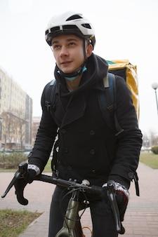 Uomo che lavora nel servizio di consegna, andare in bicicletta in città, indossando uno zaino termico