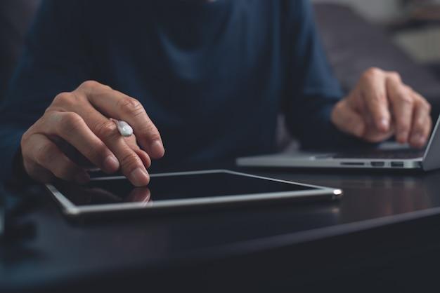 Uomo che lavora su tablet digitale e computer portatile a casa in ufficio
