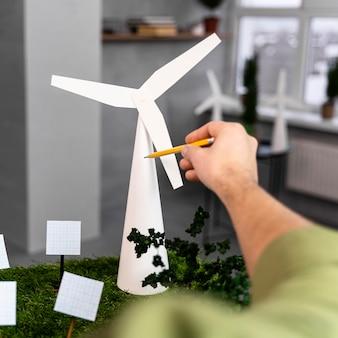 Uomo che lavora su un layout di progetto di energia eolica ecologico con turbina eolica