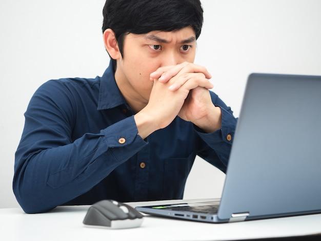 Uomo che lavora da casa e guarda il laptop sul tavolo sentendosi serio sul lavoro