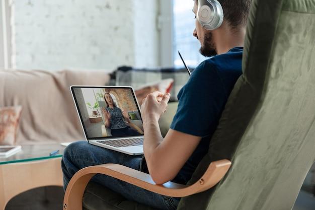 Uomo che lavora da casa, utilizzando dispositivi, concetto di ufficio remoto. il giovane uomo d'affari, manager che svolge attività con il laptop, ha una conferenza online. coronavirus, covid-19 prevenzione della diffusione del virus.