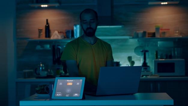 Uomo che lavora da una casa intelligente che controlla l'ambiente con gadget wifi