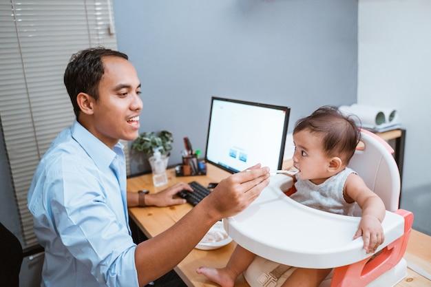 Uomo che lavora a casa e prendersi cura del suo bambino