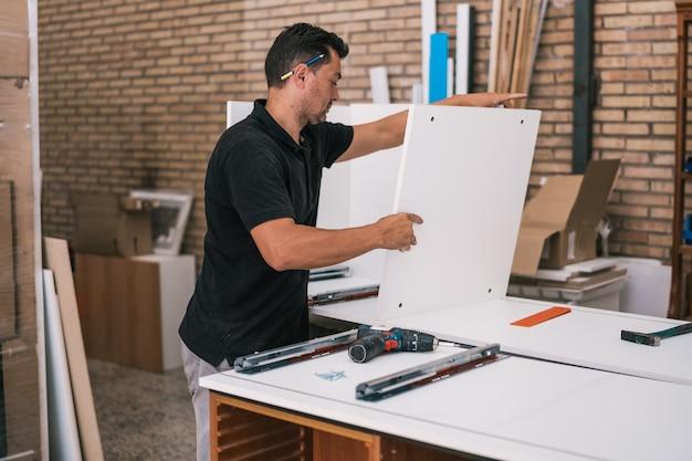 Uomo che lavora su un mobile da cucina in un'officina