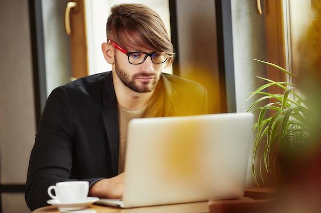 Uomo che lavora al computer portatile nel caffè