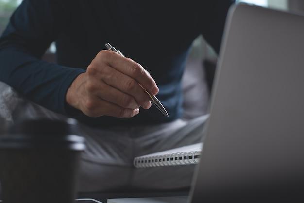 Uomo che lavora al computer portatile a casa in ufficio