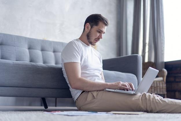Uomo che lavora al computer portatile seduto sul pavimento con il suo diario e documenti ufficiali a casa