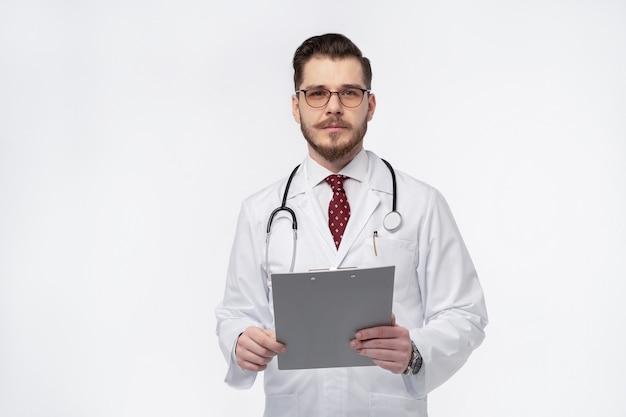 Uomo che lavora al computer portatile seduto sul pavimento con il suo diario e documenti ufficiali