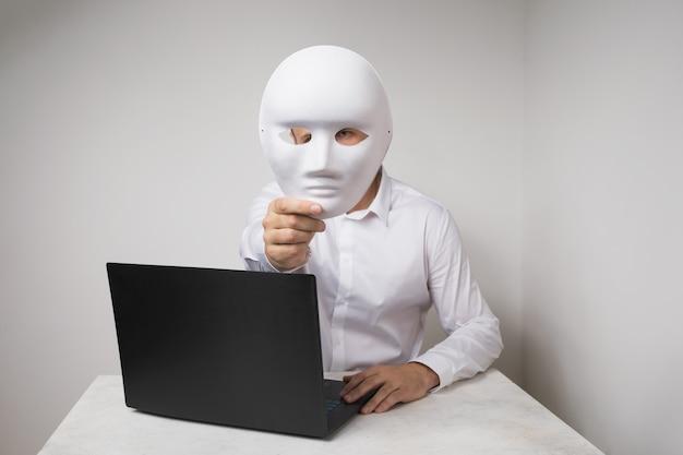 Un uomo che lavora a un laptop si copre il viso con una maschera il concetto di anonimato su internet