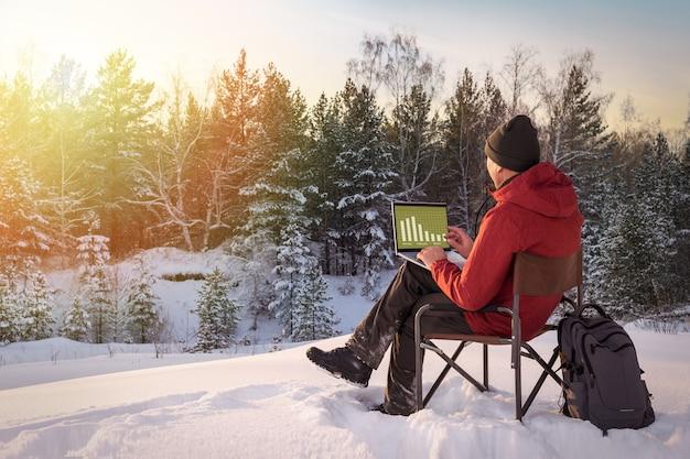 Uomo che lavora al computer portatile nella foresta ricoperta di neve al tramonto. concetto di lavoro a distanza.