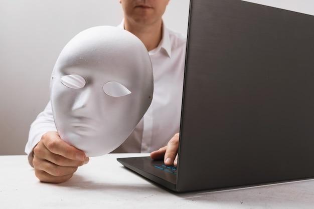 Un uomo che lavora a un laptop tiene in mano una maschera un concetto sul tema dell'anonimato su internet