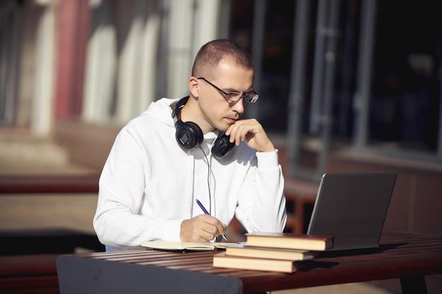 Uomo che lavora su un laptop e scrive su un notebook seduto per strada a un tavolo. distanziamento sociale durante il coronavirus