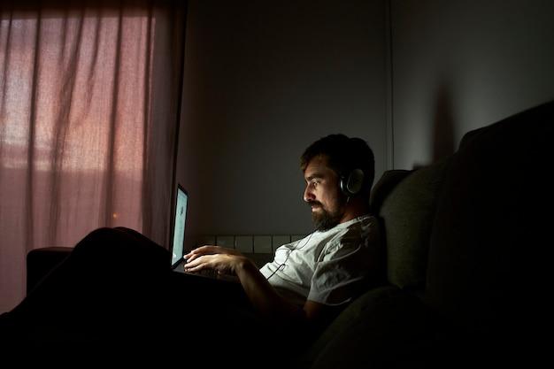 Uomo che lavora fino a tardi a casa. è seduto sul divano al buio.