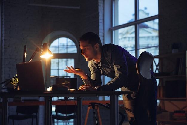 Uomo che lavora in ufficio da solo durante la quarantena del coronavirus che resta fino a tarda notte