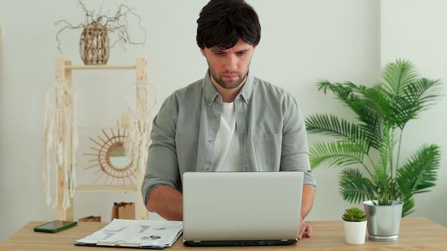 Uomo che lavora in ufficio utilizzando il computer portatile in ufficio. giovane professionista che controlla la posta elettronica e l'invio di lettere. responsabile dell'ufficio che digita sul computer portatile.