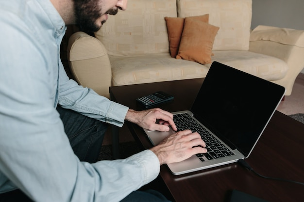 Equipaggi il lavoro online con un computer portatile che si siede sul sofà a casa. telelavoro e concetto di lavoro a distanza