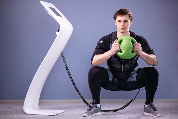 Uomo che lavora allenamento ems con palla medica