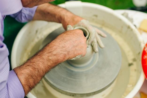 Uomo che lavora al tornio del vasaio. le mani scolpiscono una tazza da una pentola di terracotta. laboratorio di modellazione al tornio da vasaio.