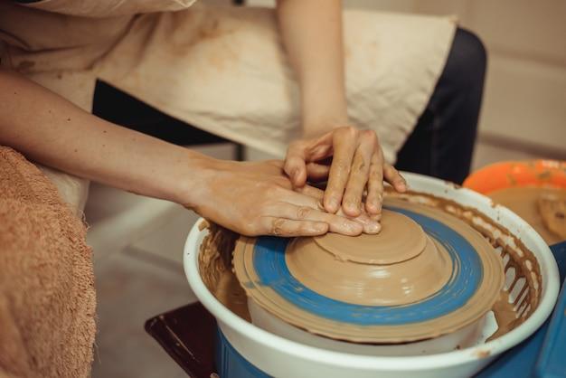 Uomo che lavora al tornio da vasaio, prepara i piatti con le proprie mani