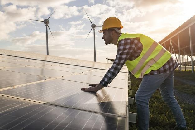 Uomo che lavora per pannelli solari e turbine eoliche - concetto di energia rinnovabile - focus sulle mani dei lavoratori maschi