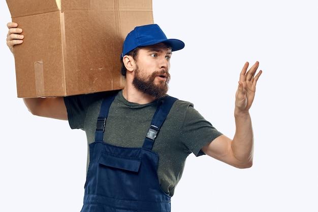 Un uomo in uniforme da lavoro con una scatola in mano il lavoro di trasporto di consegna. foto di alta qualità