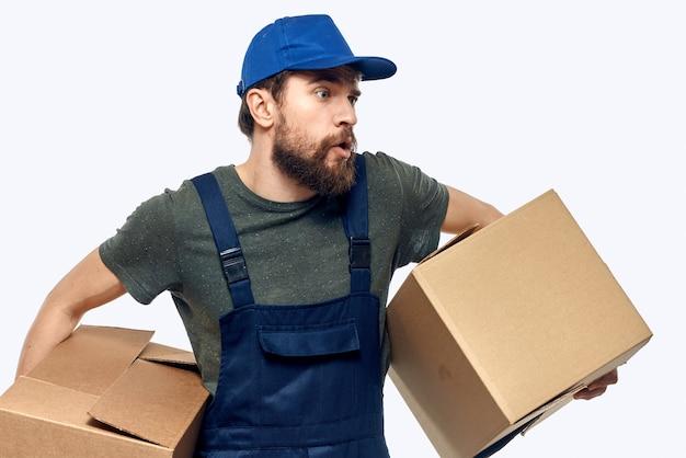 Un uomo in uniforme da lavoro con una scatola in mano il lavoro di trasporto di consegna.