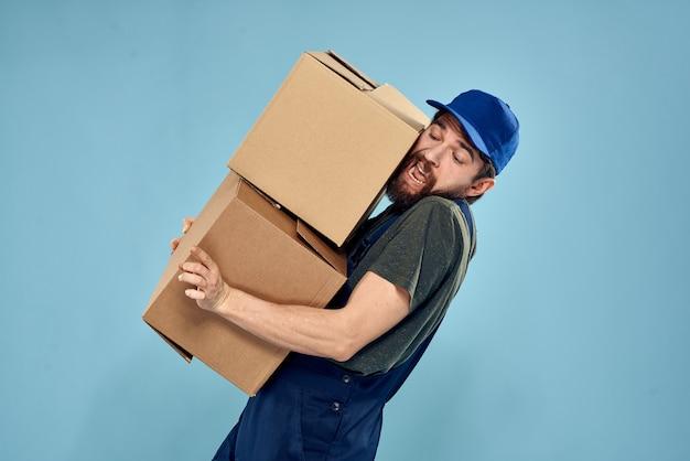 Uomo in uniforme da lavoro con scatole in mano su uno sfondo blu