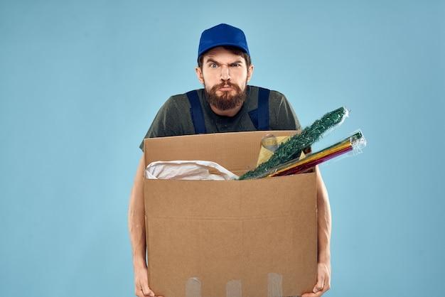 Un uomo in uniforme da lavoro con scatole nelle mani di uno spazio blu di servizio di consegna di carrozze.