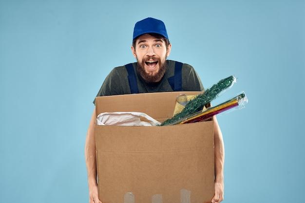 Un uomo in uniforme da lavoro con scatole nelle mani di un servizio di consegna di carrozze