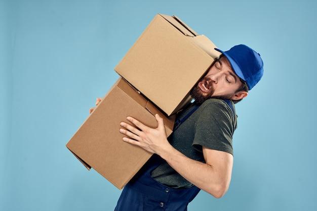 Uomo in uniforme da lavoro con scatole nello spazio blu di servizio di consegna delle mani