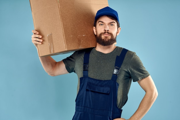 Uomo in uniforme da lavoro con scatole in mano. uomo di servizio di consegna su sfondo blu.