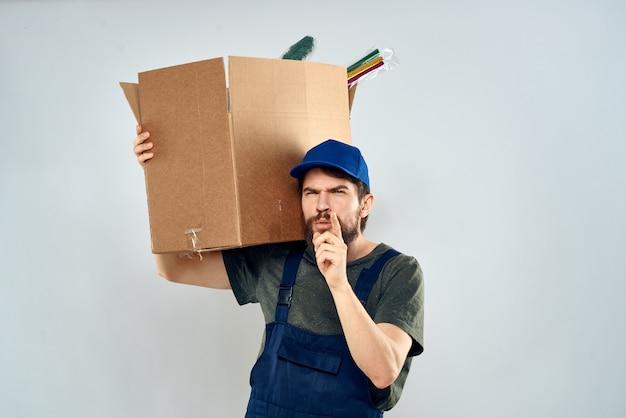 Uomo in uniforme da lavoro con scatole in mano