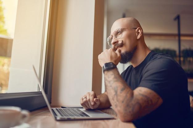 L'uomo che lavora usa un laptop con diagrammi grafici sullo schermo mentre si siede in un bar stok traders