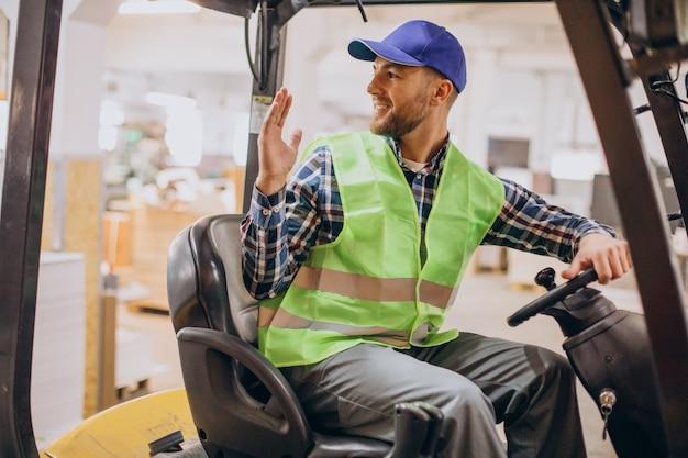 Uomo che lavora al magazzino e guida il carrello elevatore