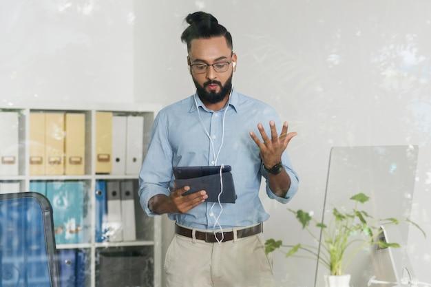 Uomo che lavora mentre controlla il suo dispositivo