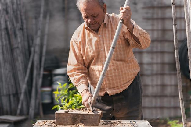 Uomo che lavora con la canna per costruire una struttura nella sua fattoria, il concetto di sforzo di un anziano