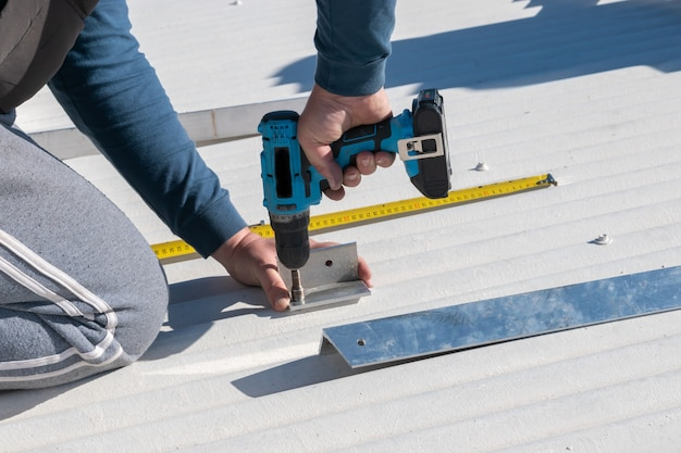 Uomo che lavora con un trapano nell'installazione del pannello solare