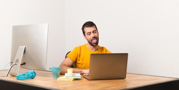 Equipaggi il lavoro con il laptot in un ufficio che mostra la lingua alla macchina fotografica che ha sguardo divertente