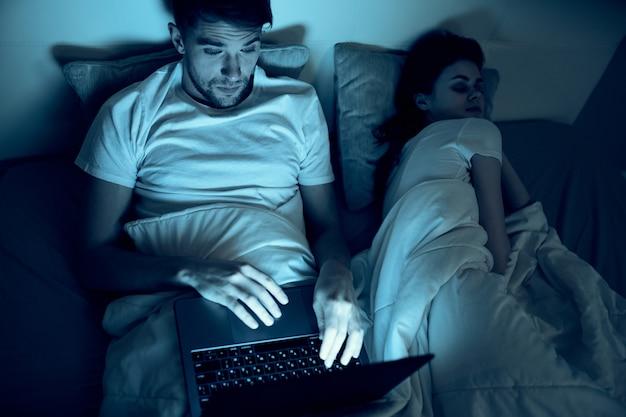 Un uomo lavora su un laptop a letto, una donna amata dorme, lavoro notturno, tradimento
