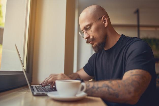 L'uomo lavora su un laptop con diagrammi grafici sullo schermo mentre si siede nella caffetteria stok trader