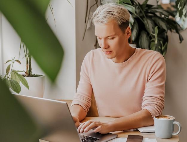L'uomo lavora sul posto di lavoro con documenti e beve caffè in un eco caffè con piante